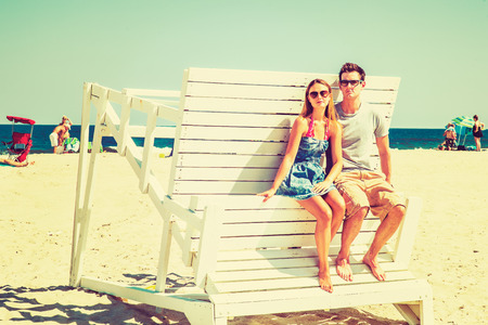relying: Young couple on the beach. Wearing glasses, barefoot, dressing in summer beach outfits, girl and guy relying on each other on a wooden structure, under strong sunshine, looking around, relaxing