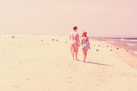 Young couple walking on the sandy beach in back view. Holding hands, guy wearing gray t shirt, yellow pants, girl dressing in strapless blue sun dress. Bridge, many birds in background. Vintage effect.  Stock Photo