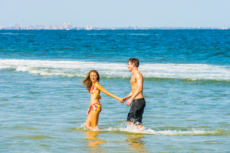 Young happy couple playing on water in the beach. Girl wearing a red, yellow patterned two piece bikini bathing suit, guy wearing a black bathing suit, holding hands each other, smiling. Stock Photo