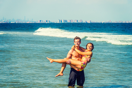On the beach. Girl wearing a red, yellow patterned two piece bikini bathing suit, guy wearing a black bathing suit, guy holding girl in his arms, standing in water of ocean. Background is New York. Stock Photo