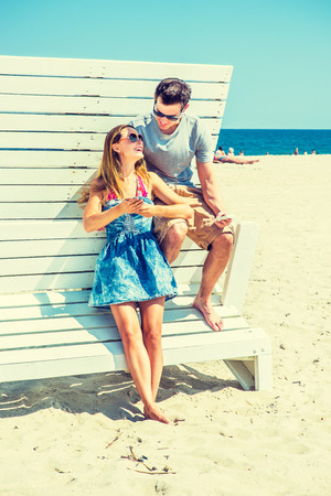 relying: Modern Vacation. Wearing glasses, barefoot, dressing in summer outfits, girl and guy relying on each other on a wooden structure, reading messages on mobile phones. Young couple on the beach.