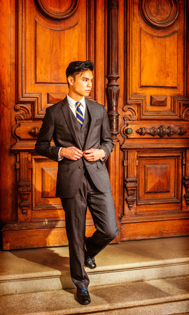 Business Man. Dressing in a black suit, patterned necktie, vest, leather shoes, a young handsome college student is walking down stairs from an old fashion style office door.