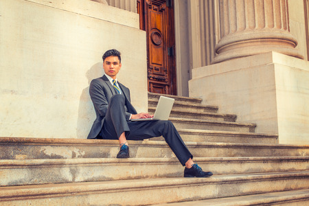 College Student Working Outside. Dressing in a black suit, patterned necktie, leather shoes, a young businessman is sitting on stairs outside an office, working on a laptop computer, thinking. Stock Photo