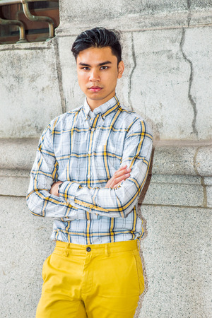 Portrait of City Boy. Wearing yellow and white, patterned shirt, yellow pants, crossing arms,  a young handsome guy is standing by old fashion style wall, confidently looking at you. Stock Photo