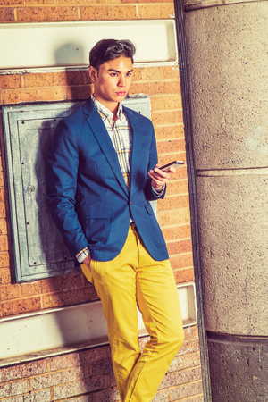 Waiting Your Phone Call. Dressing in blue blazer, yellow pants, hand holding a mobile phone.  a young handsome guy is standing by a brown brick wall, looking forward, lost in thought.