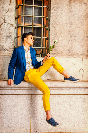 Man Missing You. Dressing in blue blazer, yellow pants, casual sneakers, a young handsome guy is sitting by a window on street, looking down at white rose on hand, thinking. Man Casual Fashion
