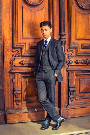 Business Man. Dressing in a black suit, patterned necktie, vest, leather shoes, hands in pockets, a young handsome college student is standing by an old fashion style office door, relaxing, thinking.