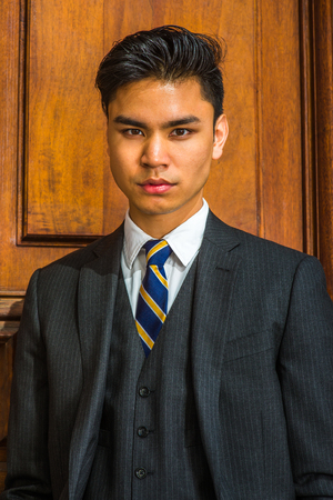 Portrait of Young Business Man. Dressing formally in three pieces black suit, patterned necktie, vest, a young handsome businessman is standing by an old fashion style office door, looking at you.