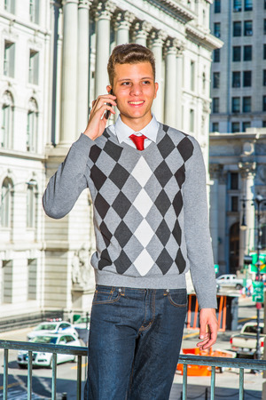 Man Calling Outside. Dressing in a black, white, gray patterned sweater, jeans, a young handsome businessman is standing in the front of an office building, smiling, talking on phone. Stock Photo