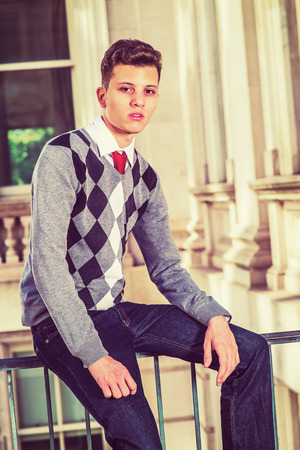 Portrait of College Student. Dressing in a black, white, gray patterned sweater, jeans, hands resting on laps, a young handsome businessman is sitting on a railing in office building, looking at you.