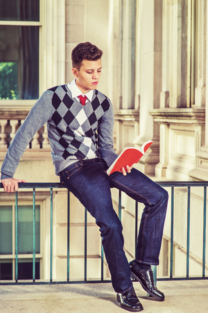 Man Reading Outside.  Dressing in black, white, gray patterned sweater, jeans, leather shoes, a young college student sitting on a railing in office building, reading a red book. Retro filtered look.