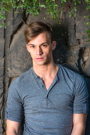 Dressing in a gray long sleeves with roll-tab Henley shirt, a young handsome guy is standing by rocks, green leaves on the top,  and charmingly looking at you. Reklamní fotografie