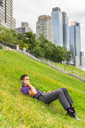Dressing in a purple shirt, gray pants and a black tie, a young handsome businessman is lying on grasses and talking on the phone.