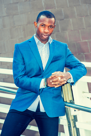 Portrait of Young Business Man. Wearing a blue blazer, black pants,, short haircut, bracelets, finger ring, a young black guy is standing against metal fences by the wall, confidently looking at you.
