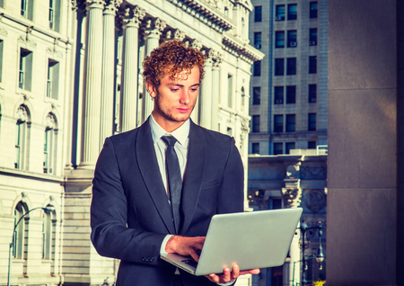 Businessman Working Outside. Dressing in black suit with Shawl Lapel, black necktie, a young sexy guy with curly hair is standing in business district, looking down, working on a computer.