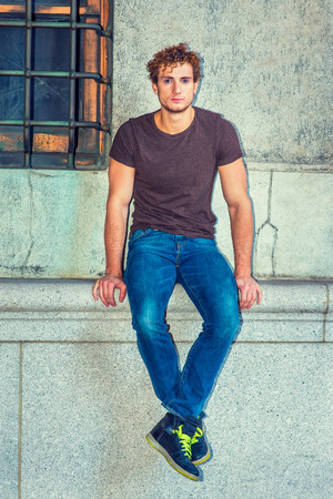 Man Relaxing Outside. Wearing dark brown T shirt, blue jeans, black sneakers, a young sexy guy with curly hair is sitting against wall by window, crossing feet, thinking, lost in thought.