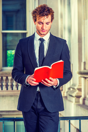 Man Reading Outside. Dressing in black suit with Shawl Lapel, black necktie, a young sexy guy with curly hair is standing inside office building, hands holding a red book, looking down, reading.