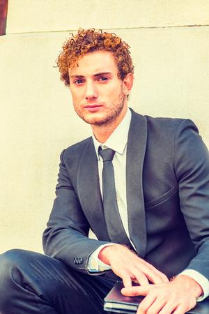 Porträt des jungen Mannes. Im schwarzen Anzug mit Schal-Revers, schwarzer Krawatte, einem jungen Mann mit lockigem Haar, der vor dem Büro hockt, einen Laptop hält und dich ansieht.