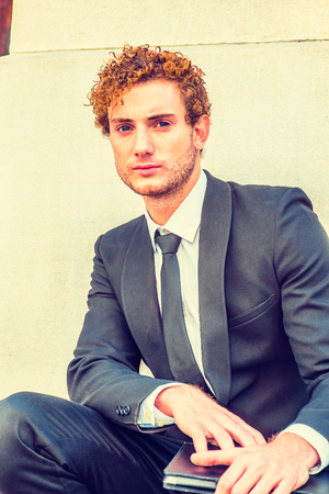 Portrait of Young Man. Dressing in black suit with Shawl Lapel, black necktie, a young guy with curly hair squatting outside office, holding a laptop computer, looking at you.