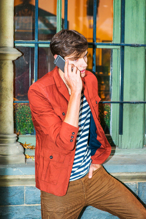 Wearing a dark reddish brown jacket, unbuttoned, striped under shit, brown corduroy pants, a young handsome guy is standing by window, making phone call on his mobile phone.