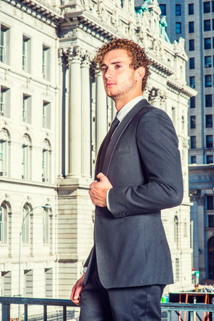 Successful Businessman. Dressing in suit with Shawl Lapel, necktie, a young sexy guy with curly hair standing in the front of vintage style office building, holding a fist.
