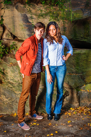 Energetic young couple standing by rocks, passionately looking at you, guy dressing in red jacket, brown pants, sneakers, girl dressing in light blue shirt, jeans, leather shoes. Autumn Outing. Imagens