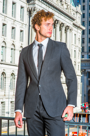 Successful Businessman. Dressing in suit with Shawl Lapel, necktie, a young sexy guy with curly hair standing in the front of vintage style office building, confidently looking forward.