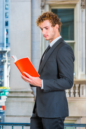 Man Reading Outside. Dressing in black suit with Shawl Lapel, black neck tie, a young sexy guy with curly hair is standing inside office building, hands holding a red book, looking down, reading.