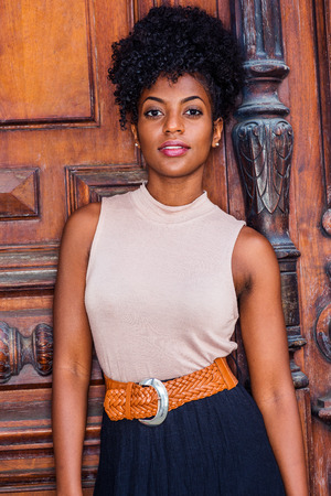 Portrait of  Young African American Businesswoman in New York. Young black female teacher with afro hairstyle wearing sleeveless light color top, black skirt, belt, standing by vintage office door.
