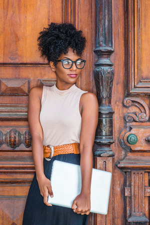 Young African American College Student with afro hairstyle, eye glasses, wearing sleeveless light color top, black skirt, belt, holding laptop computer, standing by vintage office door in New York. 写真素材