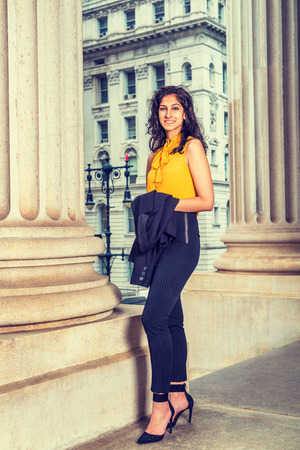 East Indian American Business Woman working in New York, wearing sleeveless orange shirt, striped pants, high heels, arm carrying jacket, standing by vintage style office building, looking forward.