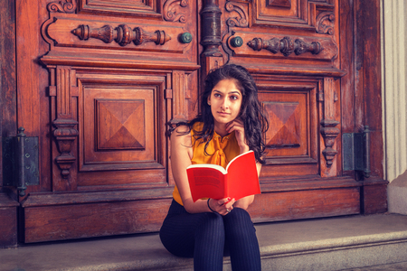 Way to Success. Power of Reading. East Indian American college student studying in New York, sitting on steps in front of vintage style library door way, reading red book, thinking, lost in thought.