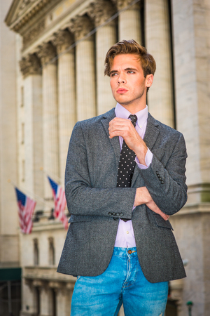 Young blonde, handsome graduate student, wearing blazer, necktie, jeans, standing by vintage style office building with American flags, looking forward. Urban casual fashion.