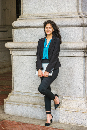 East Indian American college student studying in New York, wearing black blazer, blue shirt, striped pants, heels, holding laptop computer, standing against column, smiling.