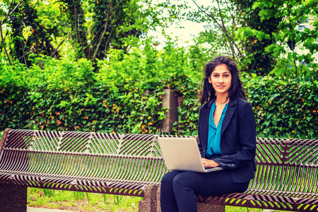 East Indian American college student studying in New York, sitting on chairs on green campus, reading, working on laptop computer. Concept of environment protection, new technology in our daily life. Imagens