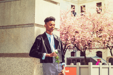 A 18 years old black student, wearing fashionable jacket, striped pants, blue dyed white shirt, standing by gate on campus, holding white rose, thinking, lost in thought. Retro effect.