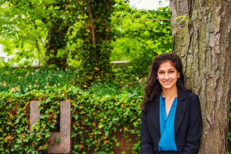 Happy East Indian American college student studying in New York, wearing black blazer, standing against tree trunk on green campus, smiling, waiting for classmates, friends.
