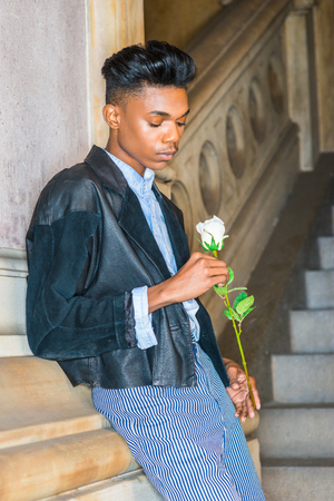 A young,18 years old college student, wearing black fashionable leather, wool mixed jacket, striped pants, hands holding flower, waiting for you in downstairs, thinking, lost in thought.