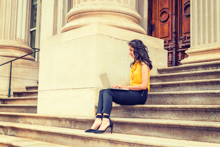 East Indian American college student studying in New York, wearing sleeveless orange shirt, striped pants, high heels, sitting on stairs outside office building on campus, working on laptop computer.