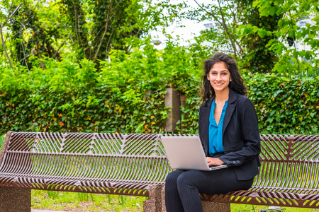 A young beautiful East Indian American college student sitting on chairs on green campus, smiling, working on laptop computer. Concept of environment protection, new technology in our daily life.