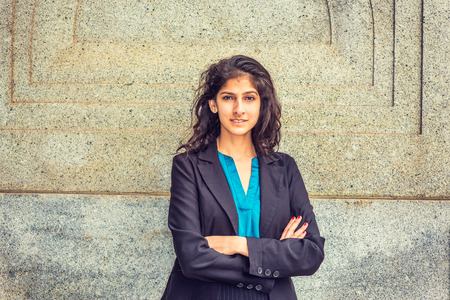 Modern East Indian American Student. Dressing in black blazer, blue under shirt, crossing arms,  a young girl with long curly hair standing by wall, smiling, looking at you.