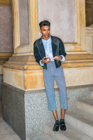 A young,18 years old student, wearing black jacket, striped pants, leather shoes, standing on stairs, leaning against column on campus, hands holding red book, reading, looking up, waiting for you.