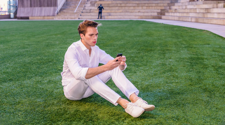 Young guy dressing in white with shirt, pants, casual fashion shoes, sitting on green lawn, reading message on cell phone. Alone, not lonely. Technology in daily life