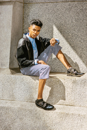 A 18 years old black student, wearing fashionable jacket, striped pants, blue dyed white shirt, leather shoes, sitting by rocky wall under sun shine, thinking.