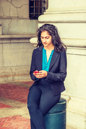 Texting. East Indian American student studying in New York, wearing black blazer, blue under shirt, striped pants, sitting by column on street, reading message on cell phone.