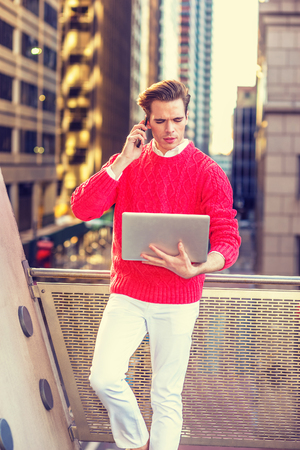 Work Remotely in New York. Young professional, wearing red sweater, white pants, standing by railing on balcony, working on laptop computer, talking on phone in same time. 版權商用圖片