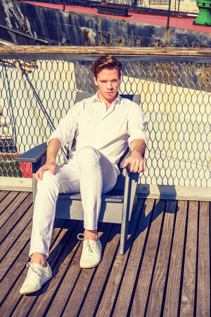 Wearing white shirt, pants, sneakers, wearing, a guy sitting on chair on deck under strong sunshine, relaxing. Boat on background.