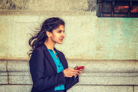 Texting anywhere. East Indian American student studying in New York, wearing black blazer, blue under shirt, standing by wall on street, reading message on cell phone.