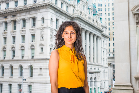 East Indian American Business Woman in New York. Wearing sleeveless orange shirt, a beautiful college student standing in the front of vintage style office building, confidently looking forward.