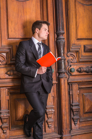 Dressing formally in black suit, necktie, white shirt, a young handsome college student standing against vintage style office door on campus, holding a red book, looking forward.